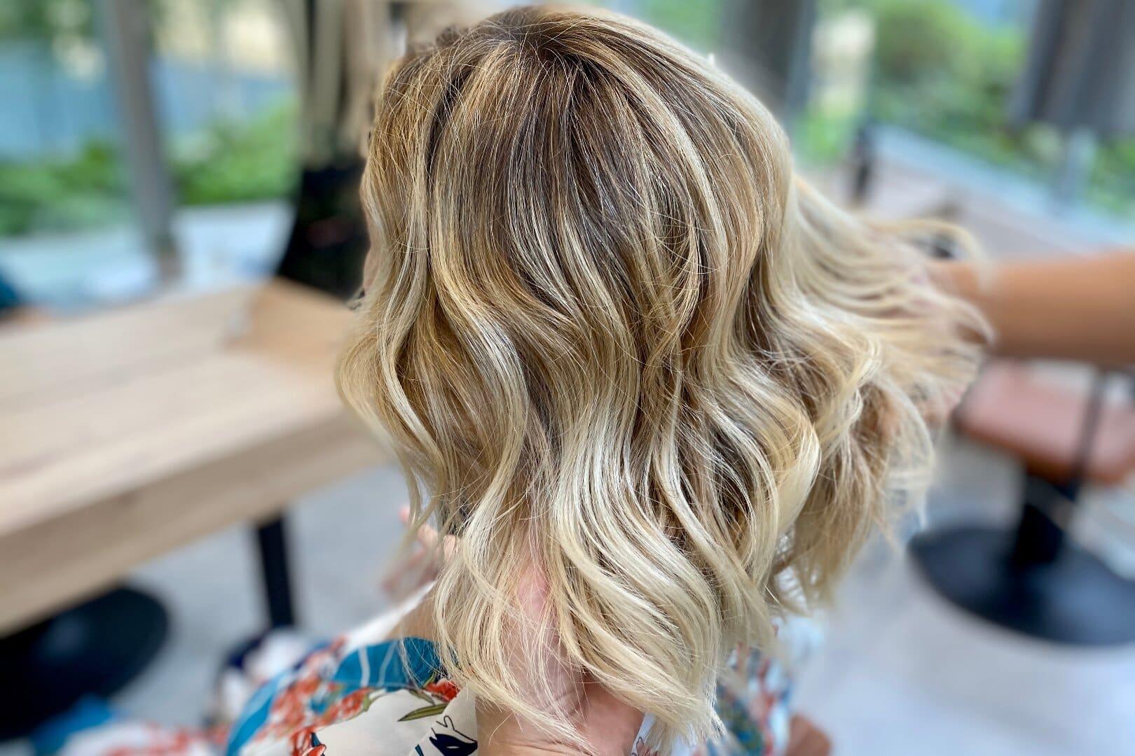Femme blonde qui réalise un balayage par un coiffeur à Maison Bis Nantes