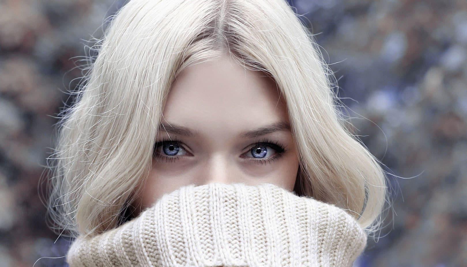 Une femme blonde avec des yeux bleues et la bouche recouverte par son pull.