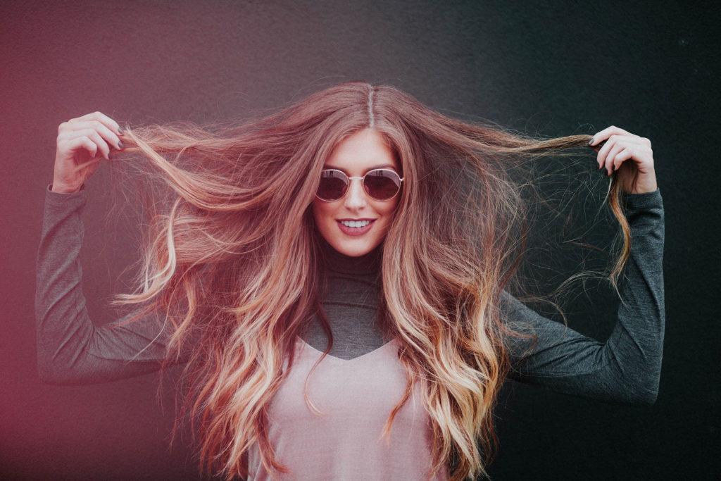 Femme avec des lunettes qui tient ses longs cheveux