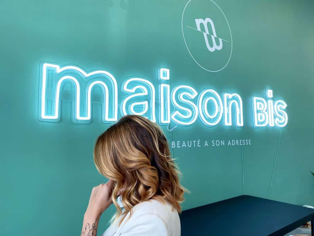 Une femme après la réalisation d'un balayage qui pose contre un mur vert à Maison Bis Nantes.