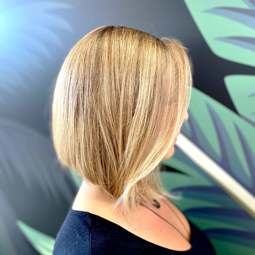 Femme aux cheveux blond avec un effet soleil en coupe carré plongeant