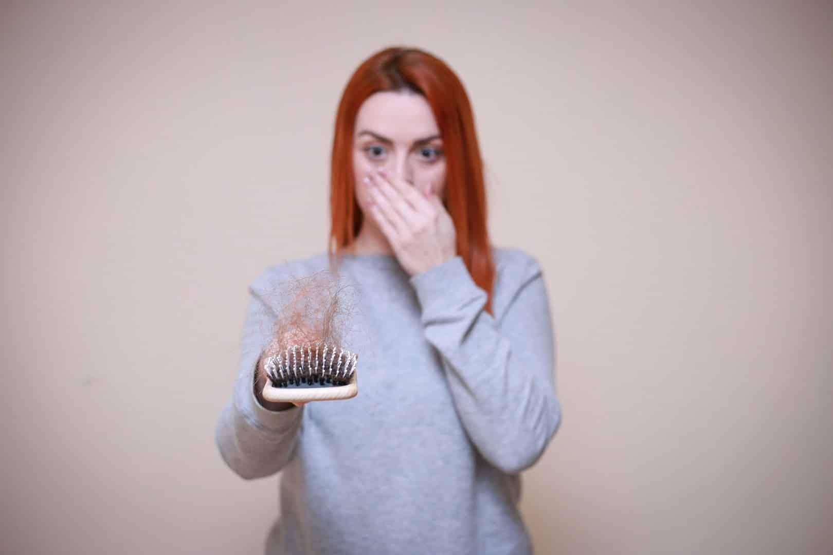 Une femme tenant une brosse avec une masse de cheveux dessus