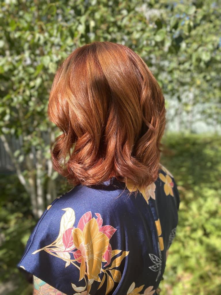 Une femme de dos avec une couleur de cheveux cuivre dans un jardin à Maison Bis Nantes