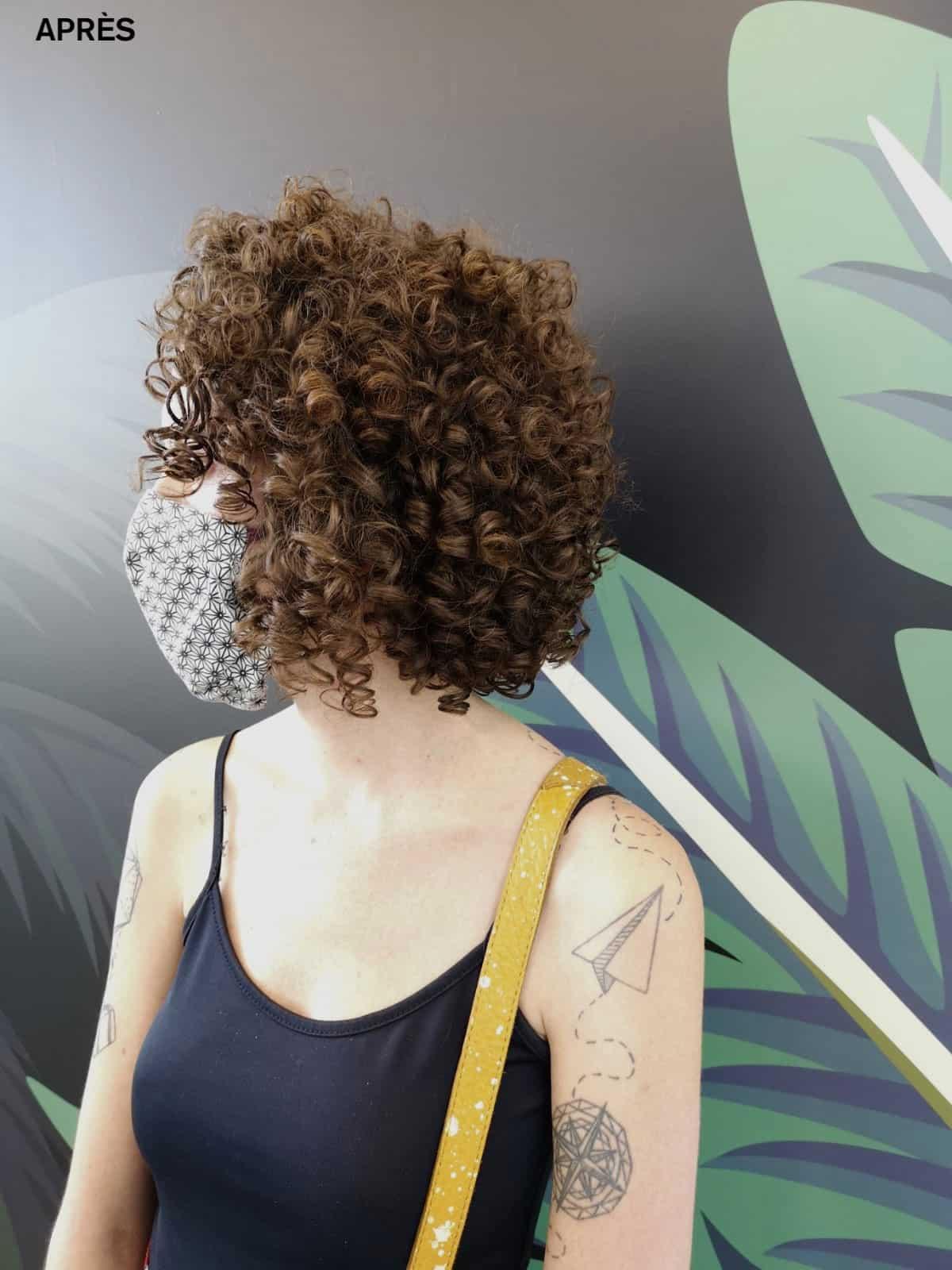 Une femme de profil avec les cheveux crépus soignés avec le wash and go.