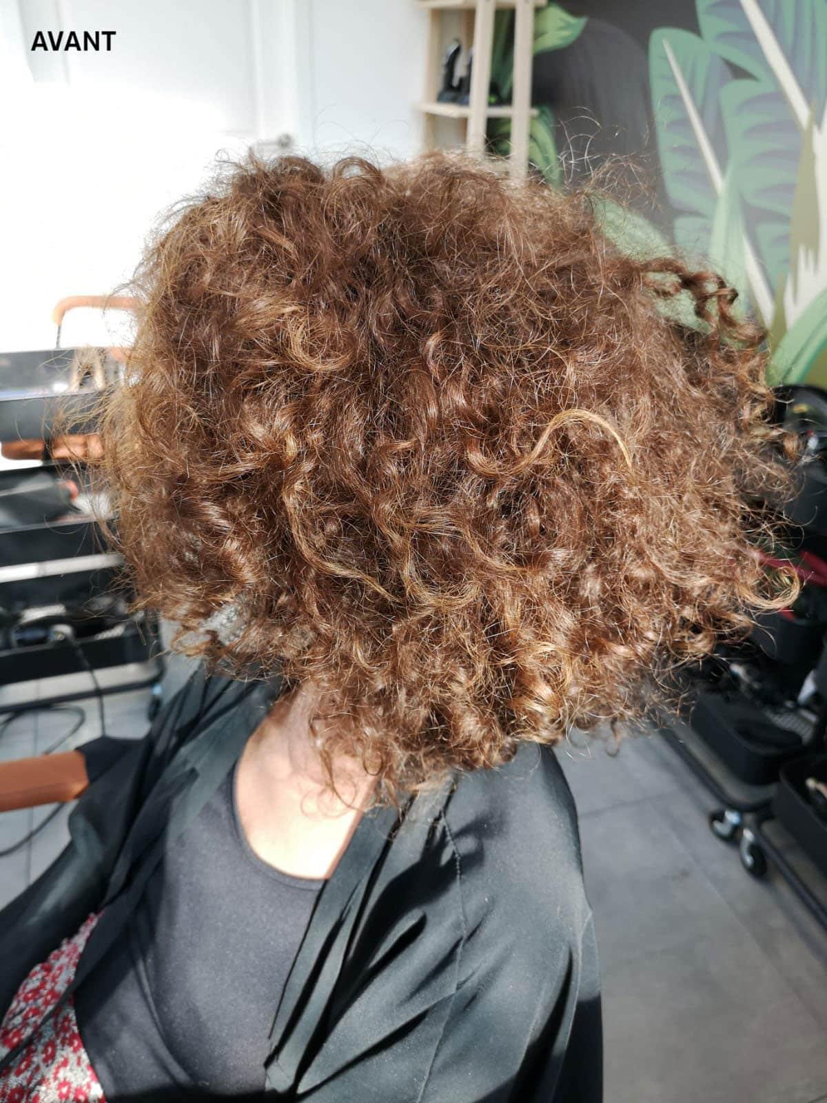 Une femme de profil avec les cheveux crépus abimés.