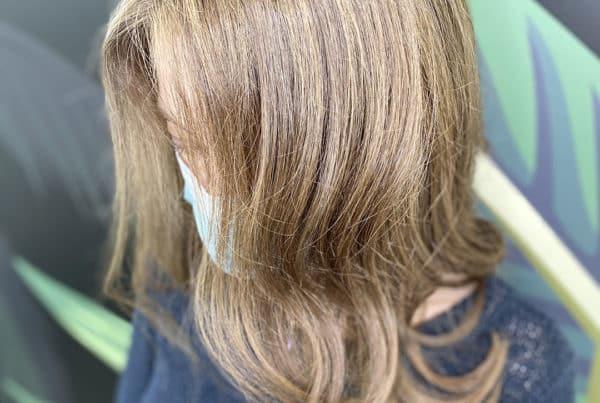 Femme blonde avec des cheveux longs de profil avec une coloration effet soleil